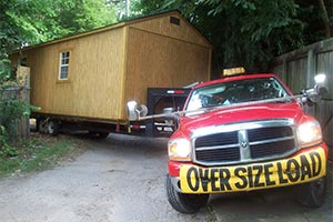 Truck skillfully pulling a portable building through a small space